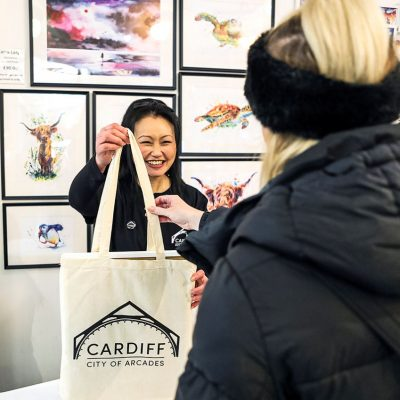 Image of woman holding a tote bag with Cardiff city of arcades branding