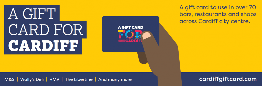 A hand holding a gift card for Cardiff. Text reads a gift card to use in over 70, bars, restaurants and shops.